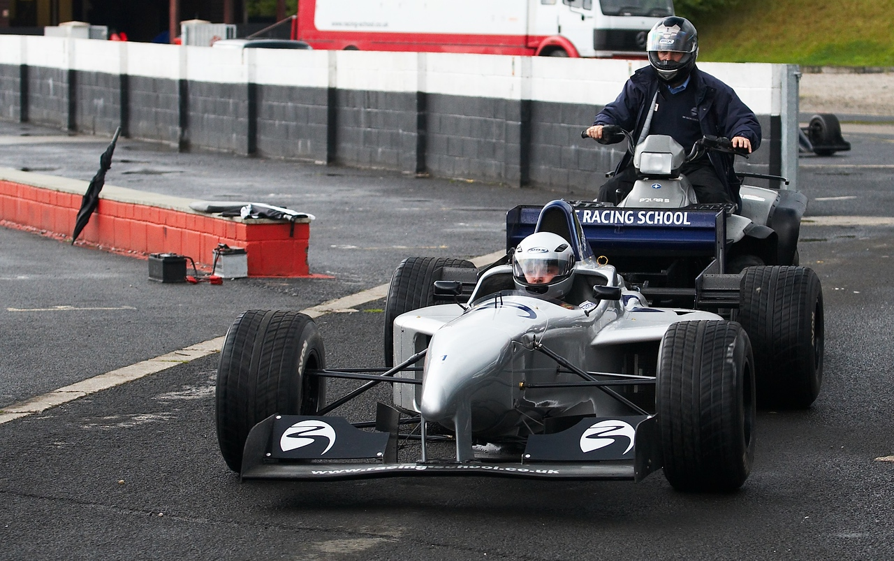 """Then it was my turn. The track was wet but it wasn't raining. This was what I had been waiting 6 months for (or all my life, depending on your viewpoint!) and it was really happening.<br /> <br /> The first very pleasant surprise was how roomy the car was. I was in the 1996 car, and it was comfortable. Heaps of room for my shoulders and knees. I was sitting in the car, remembering the F1 specific briefing where the head instructor had given us the rules...<br /> <br /> - Don't change gear, get into 4th or 5th and leave it there. These cars do WAY more miles than any F1 gearbox has any right to be expected to last, and it's the weak point of the car. He said to trust him, than a single gear would be enough to take the whole track and it would never bog down.<br /> - If you spin, hit the clutch (which you don't need if you change gears) and kill the engine.<br /> - They have a sign with """"Take it Easy"""" on it. They will display this if they believe you are driving beyond your skills or beyond the conditions. They will show it to us no more than twice. Third time is a red flag and we come in to find out what we were doing wrong and we MIGHT be allowed out for the rest of the laps.<br /> <br /> So I was sitting there in the car, strapped comfortably in, waiting for the quad bike to push start us (again, a clutch saving mechanism - plus it's hard to start an F1 car without a lot of practise) and one of the instructors comes over to me...<br /> <br /> """"Neil, I know Neil (the head instructor) said to choose a gear and stick to it, but feel free to play from 3rd up. Please don't use 1st or 2nd - you won't need them and in the wet they will mean an instant spin""""<br /> <br /> I grinned. I had planned to play with the gears anyway, at least in the last few laps."""