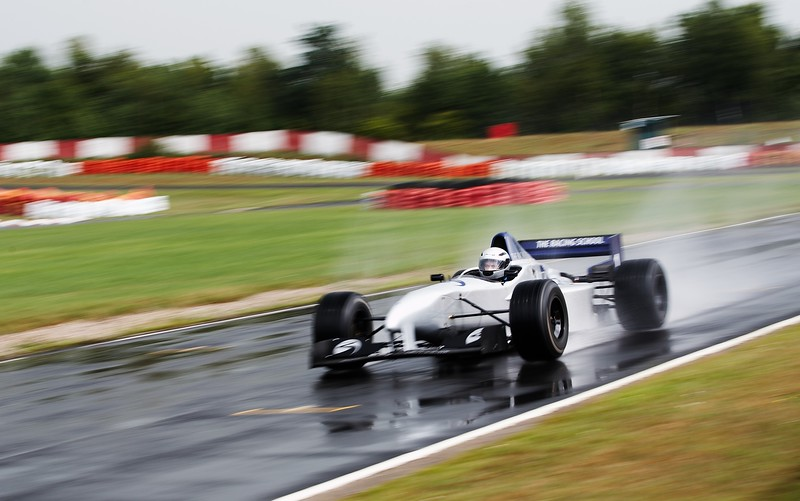 "I have always wanted to drive a Formula 1 car. I hold no serious aspirations of being an F1 driver, and at my age, it's clearly impossible I'll ever get to drive one on merit. So what's the next best thing?  Yep, pay someone lots of money to let me have a go in their old F1 car. It turns out there are a few places around the world that do this.  At the top end, there's Ferrari's Client Services, but this carries a price tag of $[if you have to ask, you can't afford it], so they weren't a serious choice...  But there are a number of places offerring pretty realistically priced driving experiences, some in France, at least one in the UK, and some others dotted about. The prices aren't silly - starting at about $3000 NZD (including other cars as well) and going up to about $10k or so.  It just so happened that I was planning a trip to Prague in July 2010 to photograph the World Ultimate Club Champs and this is conveniently close to Britain where one of the F1 drive places was based. So I made some enquiries. It went something like this...  --------------------------------------------------------------------------------------------------------------------------- <i>Me - ""So, I'm going to be near Britain from about July 11th-16th. I would like to drive your F1 car. Are you seriously saying that for just $3000 I can drive a real F1 car as fast as I like around your track?""  Them - ""Yes""  Me - ""Sold""</i> ---------------------------------------------------------------------------------------------------------------------------  There was in reality a bit of back and forth about dates, pricing, licenses and physical properties of the intended driver (ie. weight and dimensions) but it all worked out. Fortunately my broad shoulders would fit in the car. Yeah, my shoulders, that was it... shoulders.  Now all I had to do was get from Prague to Britain, find a place to stay and find a way to get around.  --------------------------------------------------------------------------------------------------------------------------- <i>Me - ""Dave, where do you live and do you have a spare room on or aboutthe 11th-16th July?""  Dave - ""Well Neil, we live about an hour from [the F1 drive experience] and yep, you can stay with us""  Me - ""Sold""</i> ---------------------------------------------------------------------------------------------------------------------------  So that was almost everything sorted. Dave was catching up on a lot of work after the WUCC event so I had to find a way to get to the circuit and someone to take photos.., Fortunately my sister and her partner live a few hours away...  --------------------------------------------------------------------------------------------------------------------------- <i>Me - ""Tina, I'm gonna be in the UK, near Lancaster on about the 11th-16th July to do the F1 drive experience thing, do you think you possibly coul.......""  Tina(Interrupting) - ""Awesome! We'll take some time off and come down and see you, need a ride to the track from where you're staying?""  Me - ""Sold""</i> ---------------------------------------------------------------------------------------------------------------------------"