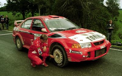 Risto Mannisenmaki checks tyre pressure on Tommi Makinen's Mitsubishi Lancer Evo V.