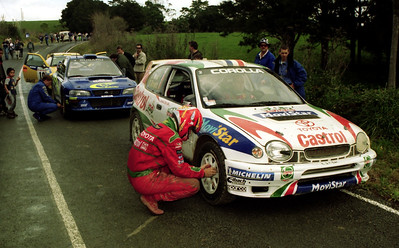 Denis Giraudet checks tyre pressure on Didier Auriol's Toyota Corolla WRC.