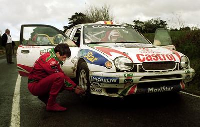 Luis Moya checks tyre pressure on Carlos Sainz's Toyota Corolla WRC.