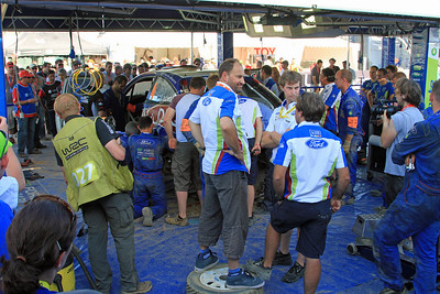 Ford mechanics and scrutineers examine Jari-Matti Latvala's crashed car to see if it can be repaired for Day 3.  The guy standing on the tyre is Ford's WRC Technical Director Christian Loriaux.