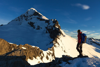 Male mountaineer stands on Shipowner Ridge overlooking the North West Ridge of Mount Aspiring, Mount Aspiring National Park