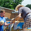 Albert Lemond hands a cantaloupe to Zack Sutton to carry in to the Senior Citizen Center on Wednesday, August 10.