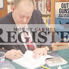 Jamey Walston / The Register<br /> <br /> Photo illustration of Mark Garrison, local author, signs a copy of his book during his book signing event at the Mount Carmel Public Library on Jan. 15. He also read a portion of his book for everyone who attended.