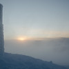 Blowing snow and fog at sunset.