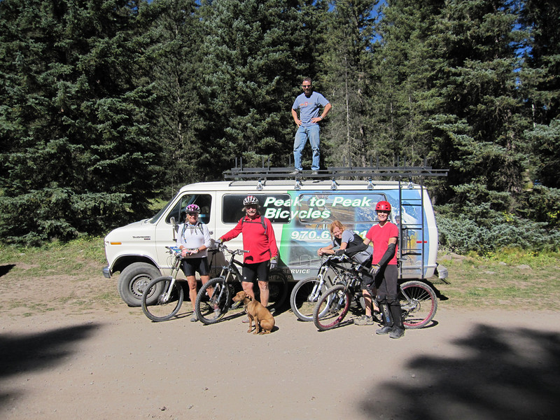 Randy, owner of Peak to Peak Bicycles, and our shuttle driver stands on top of his van.  We pay $15/rider to get up to the Blue Lakes trail head at 9.4K feet.  From left to right - Janet, Pat, Shannon and Jeannie await the ride start.  The dog's name is Sweetie and runs the 13 mile trail with ridiculous ease.