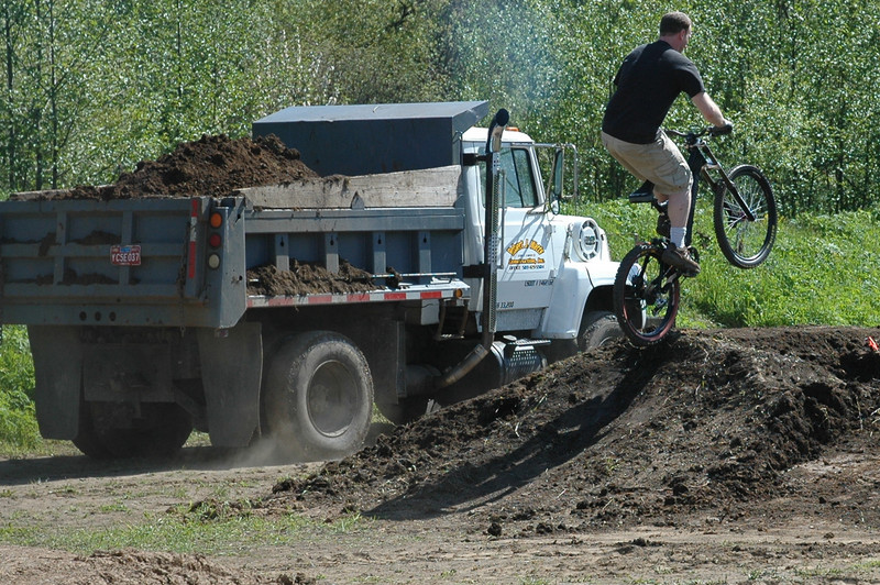 Keith testing lip of jump as next load of dirt trucked in