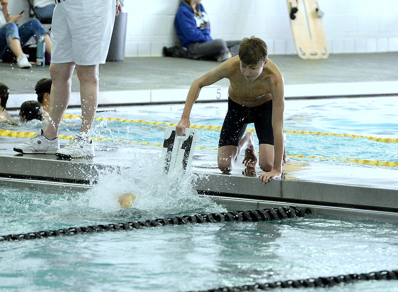 Mountian View's Max Bridges pulls the board out of the water as he counts for teammate Jayden Bishop during the 500 freestyle at Saturday's Mountain View Invitational.