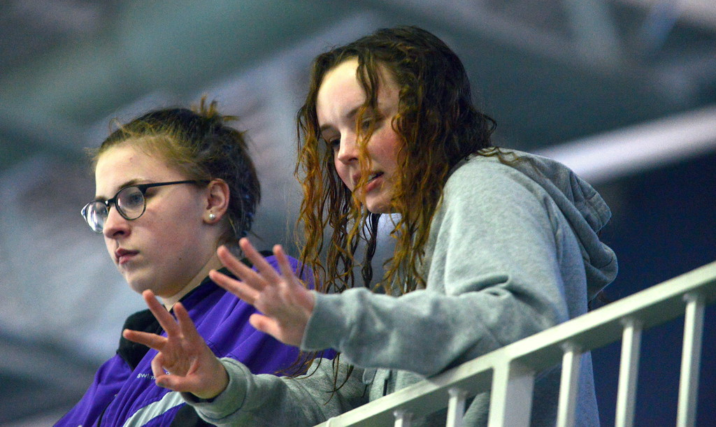 . Mountain View\'s Abby O\'Donnell (right) and Grace Peterson talk to their teammates from above the deck at Saturday\'s Mountain View Invitational at the Mountain View Aquatic Center. (Mike Brohard/Loveland Reporter-Herald)