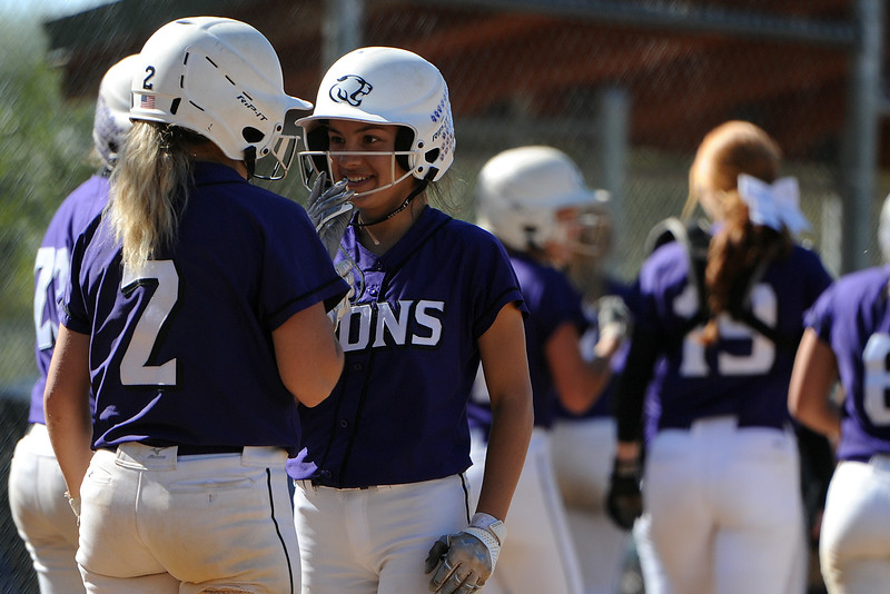 Mountain View's Jaelyn Taylor, right, talks to Kamryn Leoffler (2) after Leoffler's home run during the 4A Region 6 tournament on Saturday, Oct. 13, 2018 at Barnes Complex in Loveland. (Sean Star/Loveland Reporter-Herald)