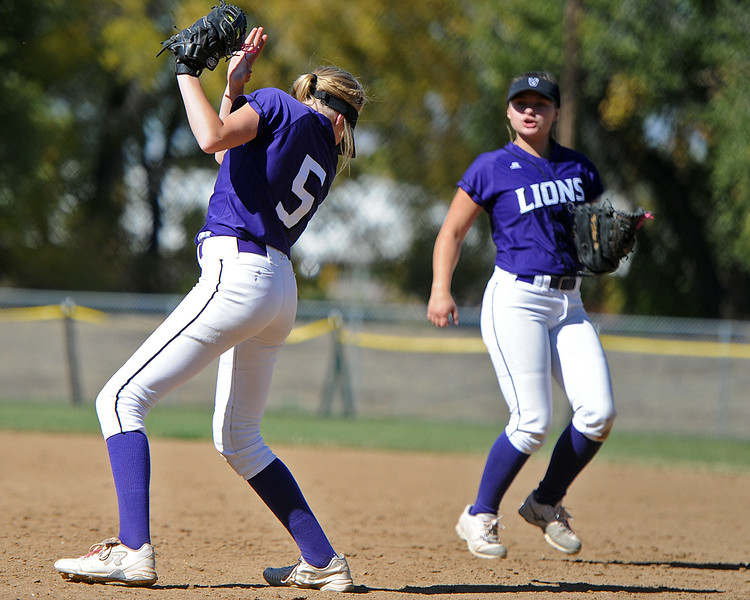 Mountain View's Harley Duke (5) looks away from the sun as she makes a catch next to teammate Morgan Jewell during the 4A Region 6 tournament on Saturday, Oct. 13, 2018 at Barnes Complex in Loveland. (Sean Star/Loveland Reporter-Herald)