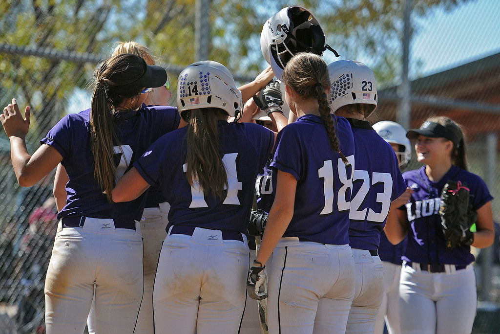 . Mountain View teammates surround Kamryn Loeffler after her home run during the 4A Region 6 tournament on Saturday, Oct. 13, 2018 at Barnes Complex in Loveland. (Sean Star/Loveland Reporter-Herald)