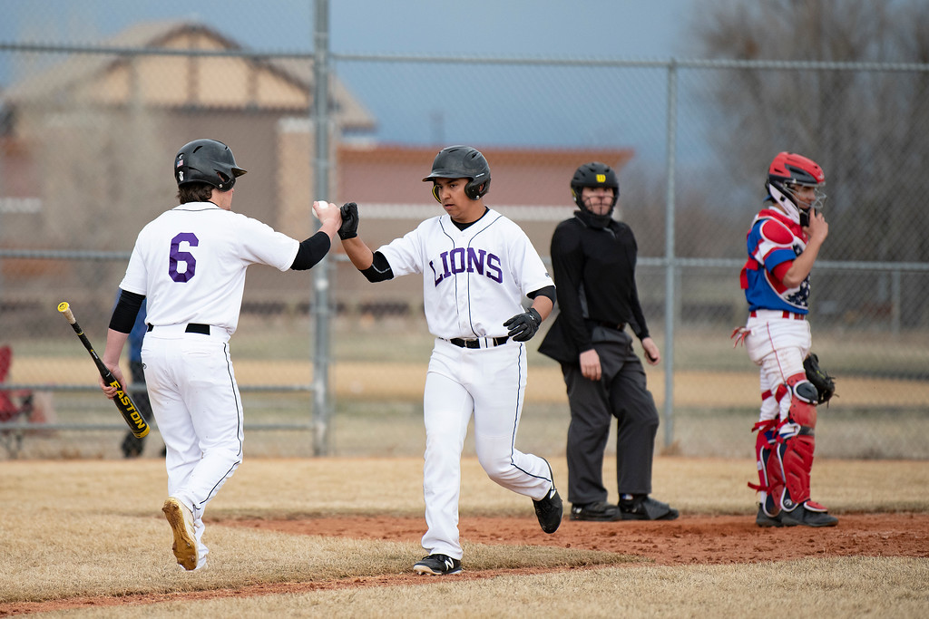 . Mountain View\'s Jacob Sanchez gets some props from teammate Chad Baumann after crossing home plate during a game against Centaurus at Greg Brock Field on Friday, March 22, 2019. The Lions defeated Centaurus 4-3.