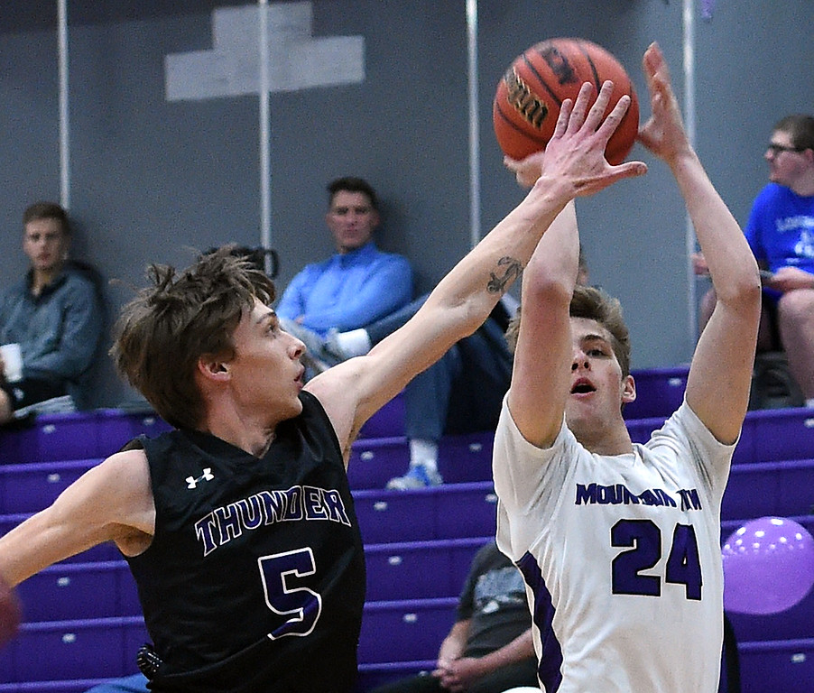 . Mountain View\'s Logan Harrison shoots a three pointer as Discovery Canyon\'s Daryn Whisman tries to block during their game Wednesday, Feb. 20, 2019, at Mountain View High School in Loveland.   (Photo by Jenny Sparks/Loveland Reporter-Herald)