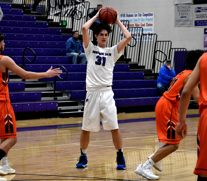Mountain View's (31) Brian Flohr looks to pass the ball as Greeley players surround him during their game on Wednesday, Feb. 14, 2018 at Mountain View High School in Loveland. Photo by Thieng Mai/Loveland Reporter-Herald.