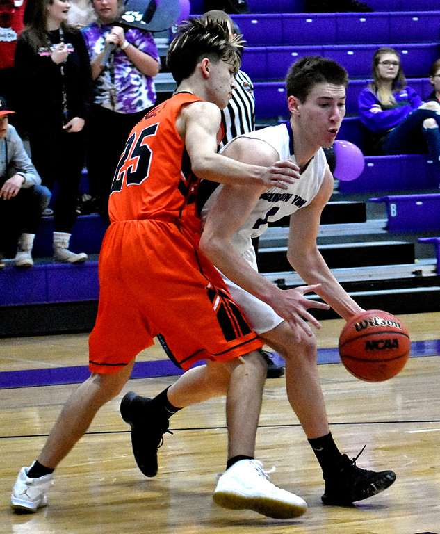 . Mountain View\'s (1) Dyson Bassett quickly dodges past Greeley\'s (25) Jackson Hayslip during their game on Wednesday, Feb. 14, 2018 at Mountain View High School in Loveland. Photo by Thieng Mai/Loveland Reporter-Herald.