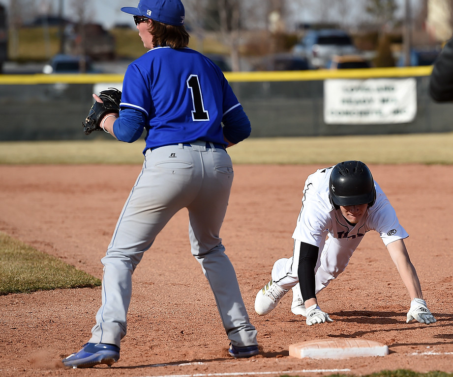Mountain View's (12) Dylan Naughton tries to get back to first as Longmont's (1) Hayden Carson waits for the ball Wednesday, March 21, 2018, during their game at Mountain View in Loveland.  (Photo by Jenny Sparks/Loveland Reporter-Herald) 12
