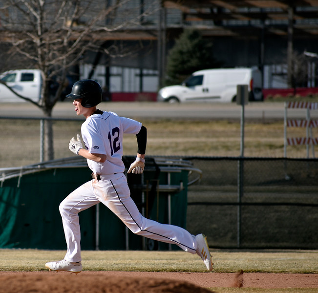Mountain Views (12) Dylan Naughton sprints from second to third base before he can be rued out by Longmont players during their game on Wednesday, March 21, 2018 at Mountain View High School in Loveland. Photo by Thieng Mai/Loveland Reporter-Herald.