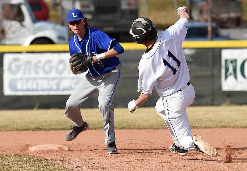 Mountain View's (11) Cade Bender slides into second base as Longmont's (3) Kascen Deeter waits for the ball Wednesday, March 21, 2018, during their game at Mountain View in Loveland.  (Photo by Jenny Sparks/Loveland Reporter-Herald)