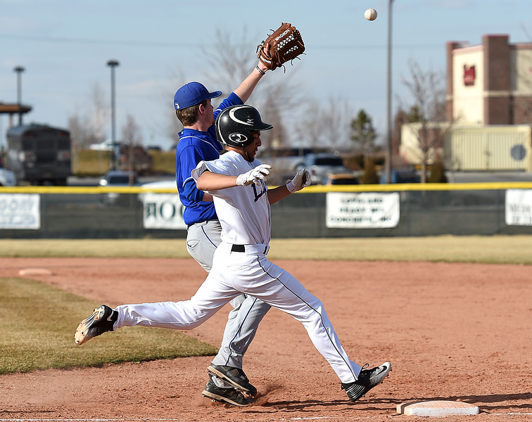 Mountain View's (13) TJ Mendoza makes it safely to first as Longmont's (18) Noah Befus catches the ball Wednesday, March 21, 2018, during their game at Mountain View in Loveland.  (Photo by Jenny Sparks/Loveland Reporter-Herald)