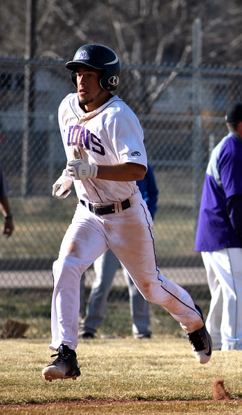 Mountain View's (13) TJ Mendoza completing his run to home base after his teammate successfully gets a hit against Longmont during their game on Wednesday, March 21, 2018 at Mountain View High School in Loveland. Photo by Thieng Mai/Loveland Reporter-Herald.