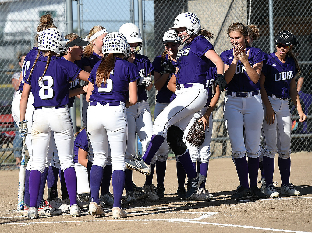 . Mountain View softball players surround home plate and cheer as teammate (9) RaLeigh Basart scores a homerun Wednesday, Sept. 20, 2017, during their game against Loveland High at Mountain View in Loveland. (Photo by Jenny Sparks/Loveland Reporter-Herald)
