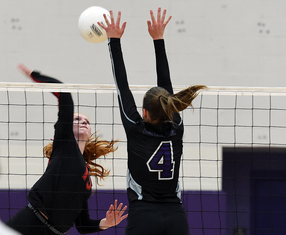 . Loveland\'s (19) Jaxin Melby spikes the ball as Mountain View\'s (4) Emilia Carmosino tries to block during their volleyball game Tuesday, Aug. 28, 2018, at Mountain View High in Loveland.  (Photo by Jenny Sparks/Loveland Reporter-Herald)