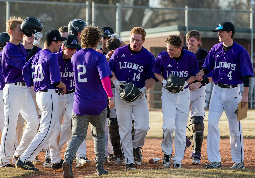 . Mountain View\'s Braden Barker (14) celebrates with his teammates after hitting a grand-slam homerun against Loveland Thursday afternoon Mar., 8, 2018 at Greg Brock Field in Loveland. The Mountain Lions beat the Indians, 11-2. (Michael Brian/For the Reporter-Herald)