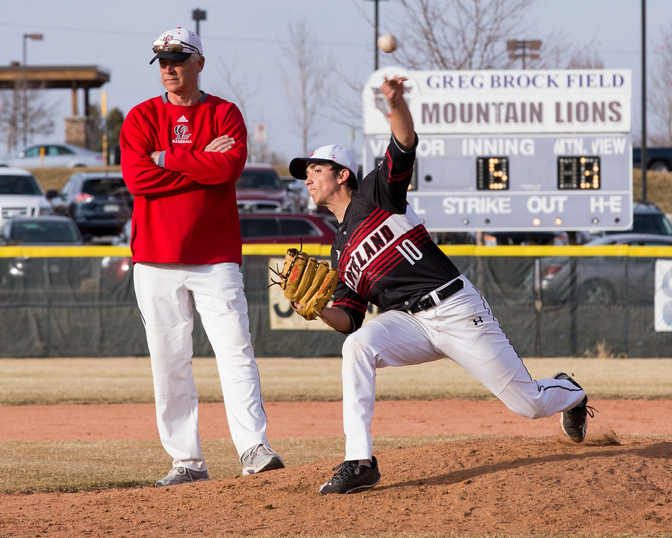 . Loveland head coach Greg Brock watches pitcher Keegan Villarreal (10) warm-up during the 5th innning Thursday afternoon Mar., 8, 2018 at Greg Brock Field in Loveland. The visiting Indians fell to the Mountain Lions, 11-2. (Michael Brian/For the Reporter-Herald)