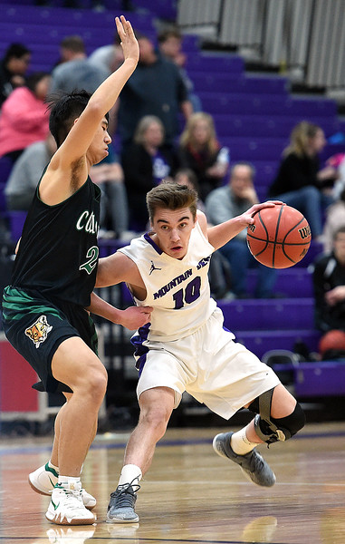 Mountain View's Shane Shadowen drives the ball down court past Niwot's Marcus Chong during their game Wednesday, Feb. 13, 2019, at Mountain View High School in Loveland.   (Photo by Jenny Sparks/Loveland Reporter-Herald)