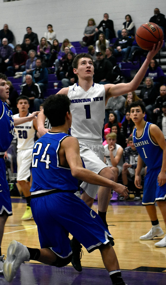 Mountain View's (1) Dyson Bassett goes for a jump shot before Pueblo's (24) Nico Martin can block him during their game on Wednesday, Feb. 21, 2018 at Mountain View High School in Loveland. Photo by Thieng Mai/Loveland Reporter-Herald.