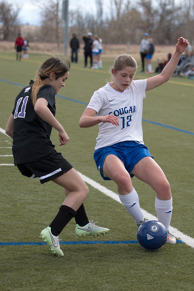 Resurrection High School's #12 Leisbeth Swift works the ball up the field as Mountain View High School's #11 Alyssa Perez tries to intercept during a game on Friday, 23 March 2017 at Loveland Sports Park.