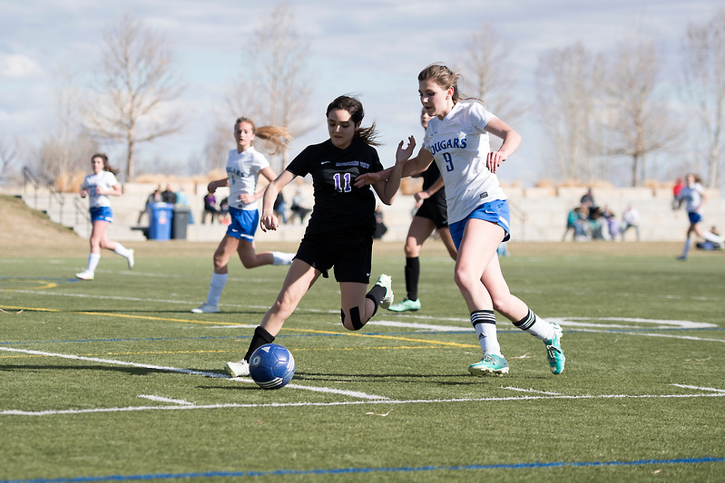 Resurrection High School's #9 Jenni Pronozuk competes with Mountain View High School's #11 Alyssa Perez for the ball during a game on Friday, 23 March 2017 at Loveland Sports Park.