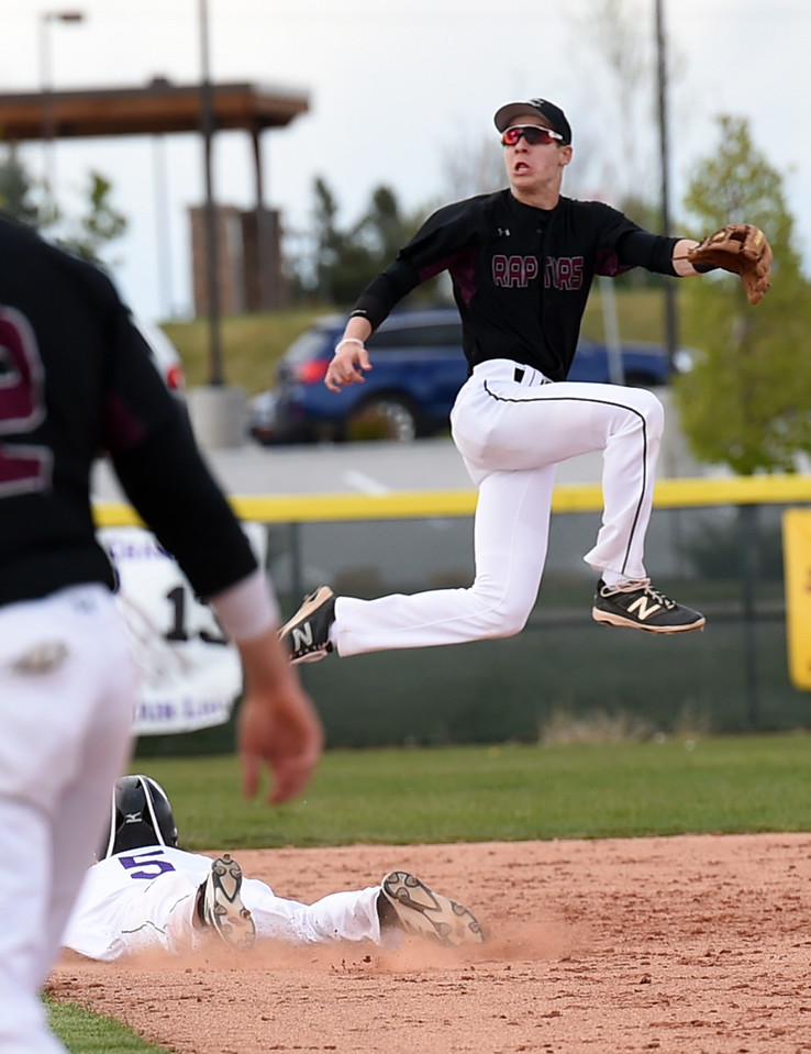 Mountain View's #5 Tanner Cartmell slides in to second base as Silver Creek's #3 Spencer Rich jumps to catch the ball Monday, May 1, 2017, during their game at Mountain View in Loveland. (Photo by Jenny Sparks/Loveland Reporter-Herald)  sc3