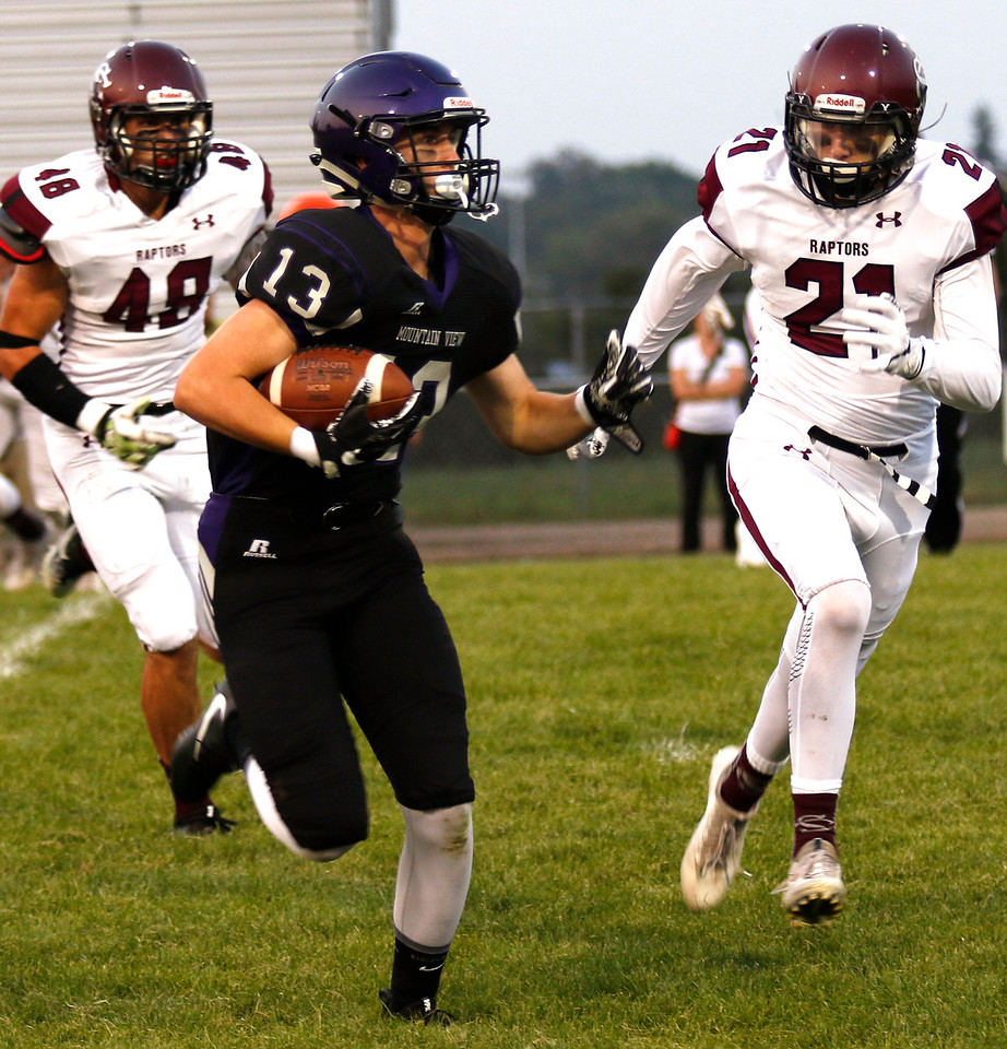 Mountain View wide reciever, senior, Preston Green #13 runs the ball try to avoid Silver Creek senior Christian Adams #21 and senior Trevor Riters at Ray Patterson Field on Sept. 7. (Photo by Lauren Cordova/ Loveland Herald-Reporter)