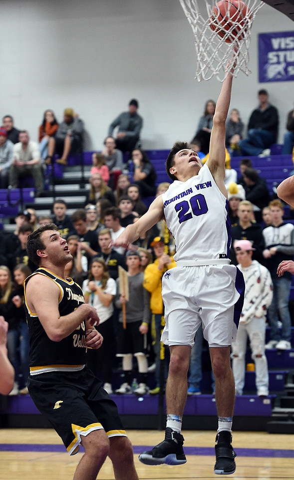 Mountain View's (20) Brexton Butcher goes up for a shot past Thompson Valley's (33) Jared Kasprzak during their game Wednesday, Jan. 3, 2018, at Mountain View High School in Loveland.  (Photo by Jenny Sparks/Loveland Reporter-Herald)