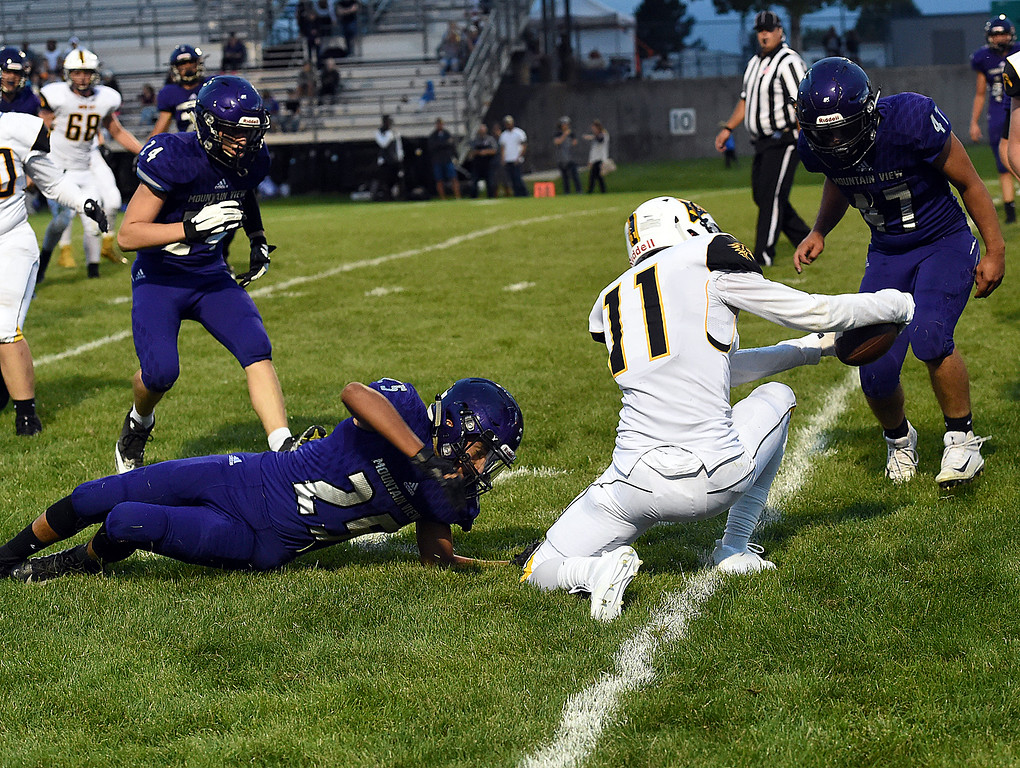 . Thompson Valley\'s Tl Smack reaches over the goal line to score after escaping tackle Mountain View\'s Cade Bender during their game Friday, Aug. 31, 2018, at Patterson Stadium in Loveland. (Photo by Jenny Sparks/Loveland Reporter-Herald)