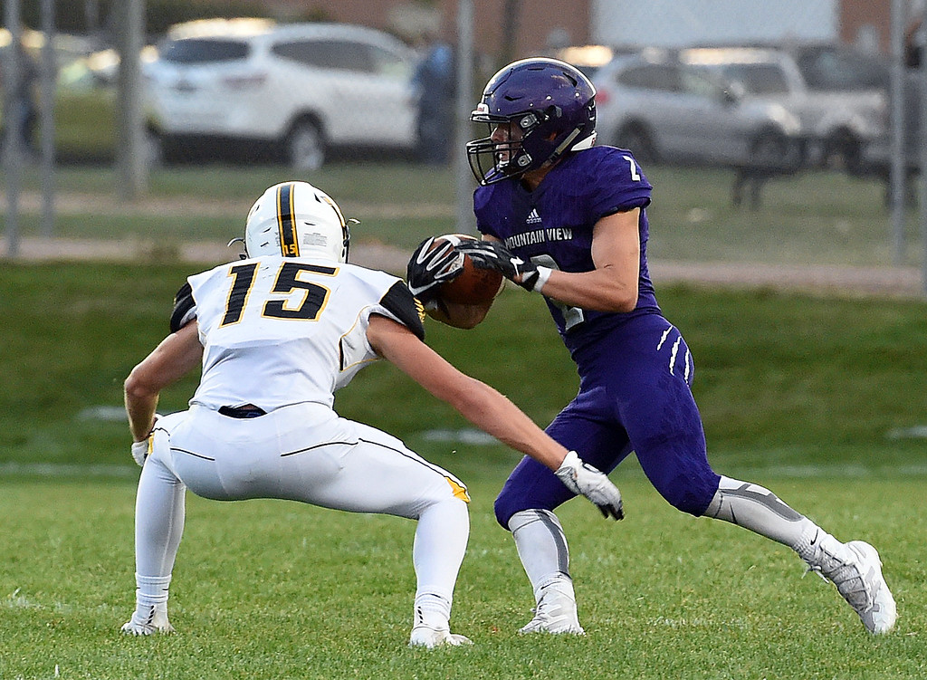 . Mountain View\'s Shane Rasico takes the ball down field as Thompson Valley\'s Trey Krelkemeier tries to tackle him during their game Friday, Aug. 31, 2018, at Patterson Stadium in Loveland. (Photo by Jenny Sparks/Loveland Reporter-Herald)