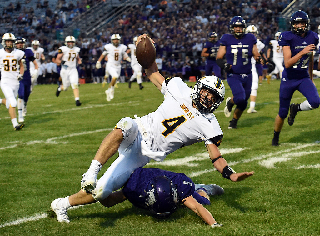 . Thompson Valley\'s Cameron Nellor gets tackled by Mountain View\'s Kamden Carwin during their game Friday, Aug. 31, 2018, at Patterson Stadium in Loveland. (Photo by Jenny Sparks/Loveland Reporter-Herald)