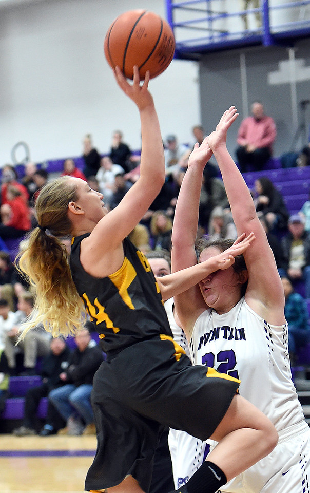 Thompson Valley's (14) Kylie Bowen goes up for a shot past Mountain View's (32) Laura Lenhart during their game Wednesday, Jan. 3, 2018, at Mountain View High School in Loveland.  (Photo by Jenny Sparks/Loveland Reporter-Herald)