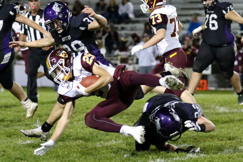 Mountain View's Braden Barker (22) and Bret Schroeder (38) tackle Windsor's Wyett Adams (25) on Thursday, Oct. 5, 2017, at Patterson Field. (Photo by Lauren Cordova/Loveland Reporter-Herald)