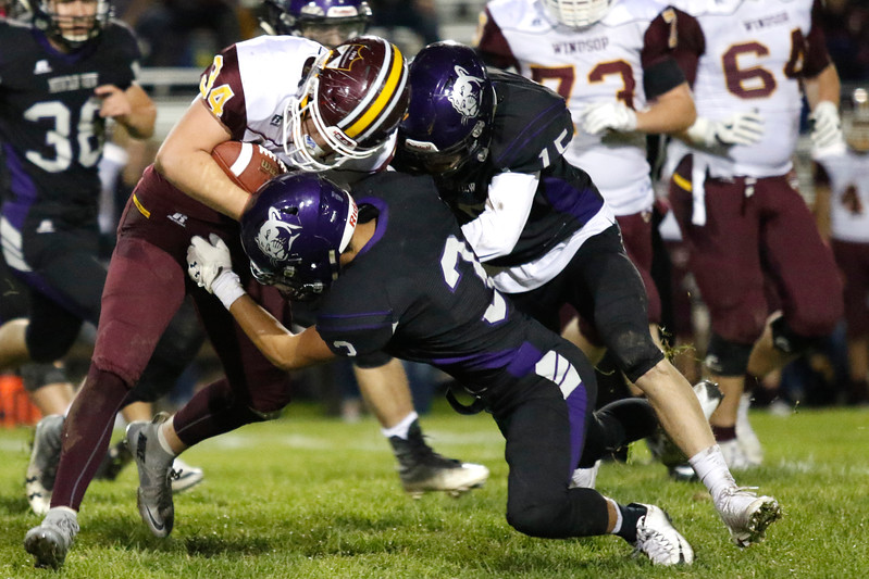 Mountain View's Josiah Baptista (3) and Kamden Carwin (15) team up to tackle Windsor's Gerald Mack (34) on Thursday, Oct. 5, 2017, at Patterson Field. (Photo by Lauren Cordova/Loveland Reporter-Herald)