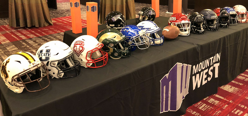 A display of the helmets of the Mountain West, with San Diego State's always drawing keen interest. (Mike Brohard/Loveland Reporter-Herald)