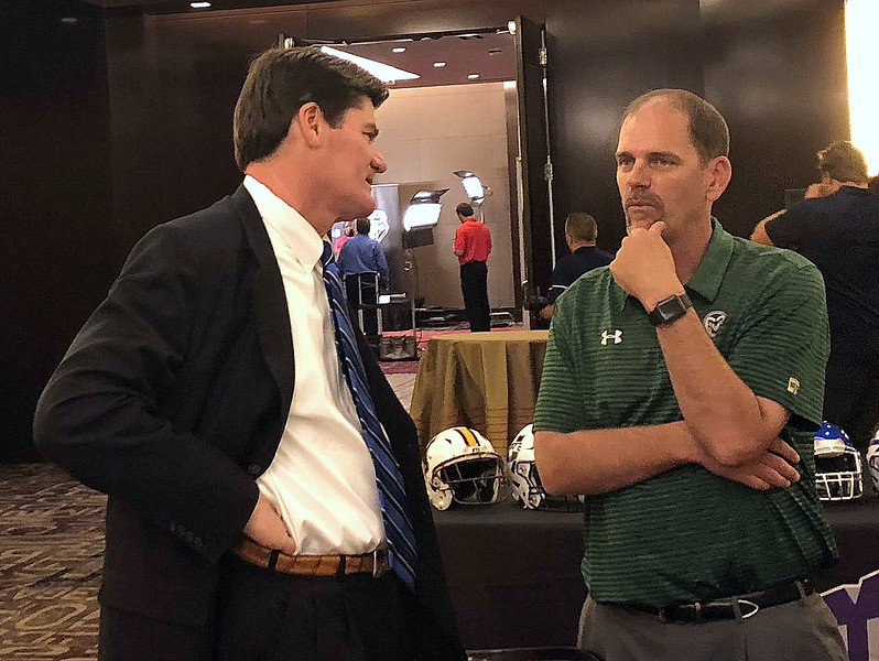 Colorado State coach Mike Bobo (right) talks with Mountain West commissioner Craig Thompson during the Mountain West Media Summit on Tuesday in Las Vegas. (Mike Brohard/Loveland Reporter-Herald)