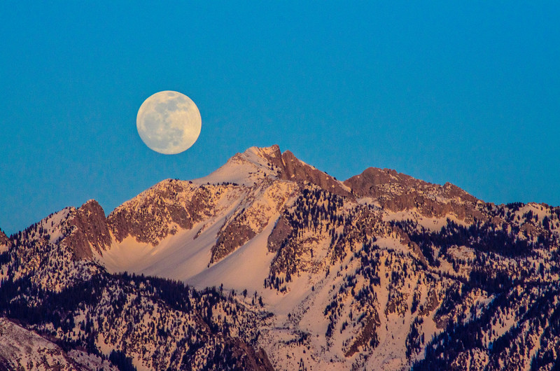 "The full moon rising over Broads Fork Twin Peaks east of the Salt Lake valley. I captured this image while standing on the top level of the UTA parking garage at 3400 W and 8600 S in West Jordan. It is one of my favorite moon shots that I've taken. However, it's not actually the full moon; this was taken two days before the full moon, so the moon was ""waxing gibbous 97%"", but it looks full to me."
