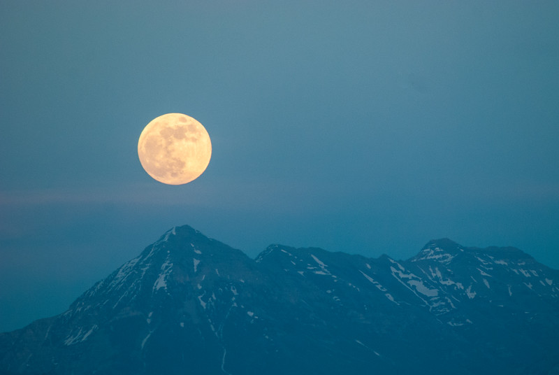The full moon above Mount Timpanogas as seen from the lawn in front of the Bingham Library in West Jordan