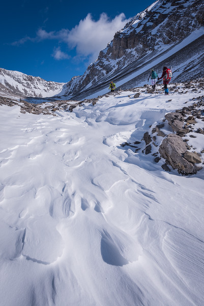 walking in the valley towards the back. wind swept snow patterns appeared on the ground.