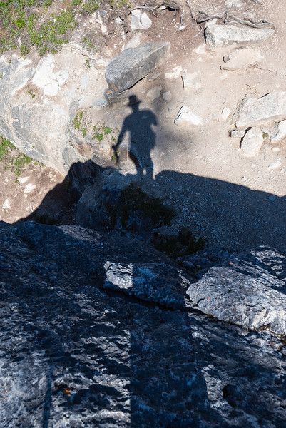 The trail crosses over the creek that feeds bow lake on a giant boulder. My shadow follows me over the top.