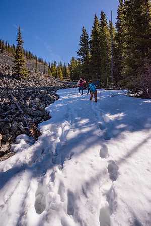 Following cairns and footsteps along the edge of the talus field in the snow.